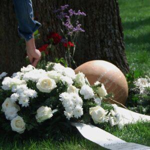 Das Foto zeigt die Gedenkkugel vor einem Baumstamm. Neben der Gedenkkugel liegen Blumen in verschiedenen Farben. Eine Hand steckt gerade eine weitere Blume dazu.